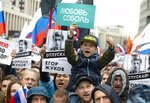 FILE - In this photo taken on Aug. 10, 2019, people with posters show portraits of detained protesters and a boy with a poster reads Lyubov Sobol react during a protest in Moscow, Russia. This summer's wave of opposition protests has pushed Sobol to the forefront of the Russian political scene. (AP Photo/Alexander Zemlianichenko, File)