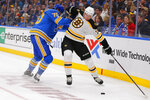 Boston Bruins' Charlie Coyle (13) alludes a check from St. Louis Blues' Oskar Sundqvist (70), of Sweden, during the first period of an NHL hockey game Saturday, Feb. 23, 2019, in St. Louis. (AP Photo/Dilip Vishwanat)