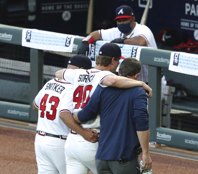 Atlanta Braves manager Brian Snitker and a trainer help pitcher Mike Soroka off the field with an apparent injury, during the third inning of the team's baseball game against the New York Mets, Monday, Aug. 3, 2020, in Atlanta. (Curtis Compton/Atlanta Journal-Constitution via AP)