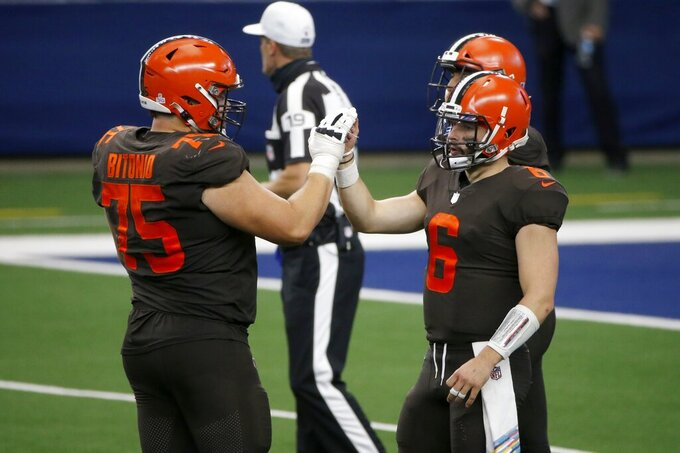 Cleveland Browns' Joel Bitonio (75) and Baker Mayfield (6) celebrate late in the second half of an NFL football game against the Dallas Cowboys in Arlington, Texas, Sunday, Oct. 4, 2020. The Browns won 49-38. (AP Photo/Michael Ainsworth)