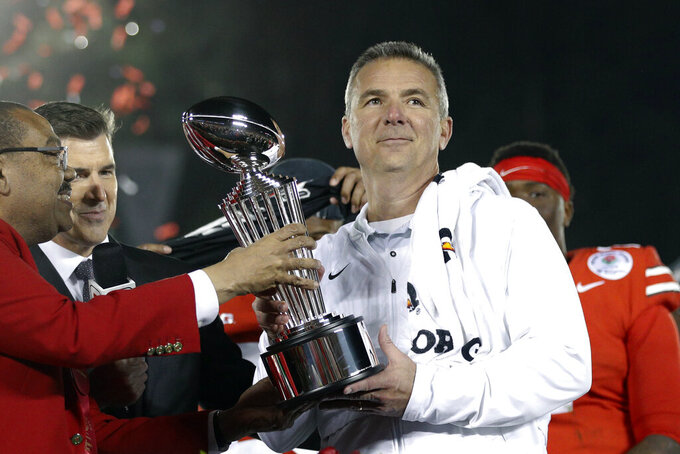 FILE - Ohio State coach Urban Meyer, right, holds the trophy after the team's 28-23 win over Washington in the Rose Bowl NCAA college football game in Pasadena, Calif., in a Tuesday, Jan. 1, 2019, file photo. A person familiar with the search says Urban Meyer and the Jacksonville Jaguars are working toward finalizing a deal to make him the team's next head coach. The person spoke to The Associated Press on the condition of anonymity Thursday, Jan. 14, 2021, because a formal agreement was not yet in place. (AP Photo/Jae C. Hong, File)