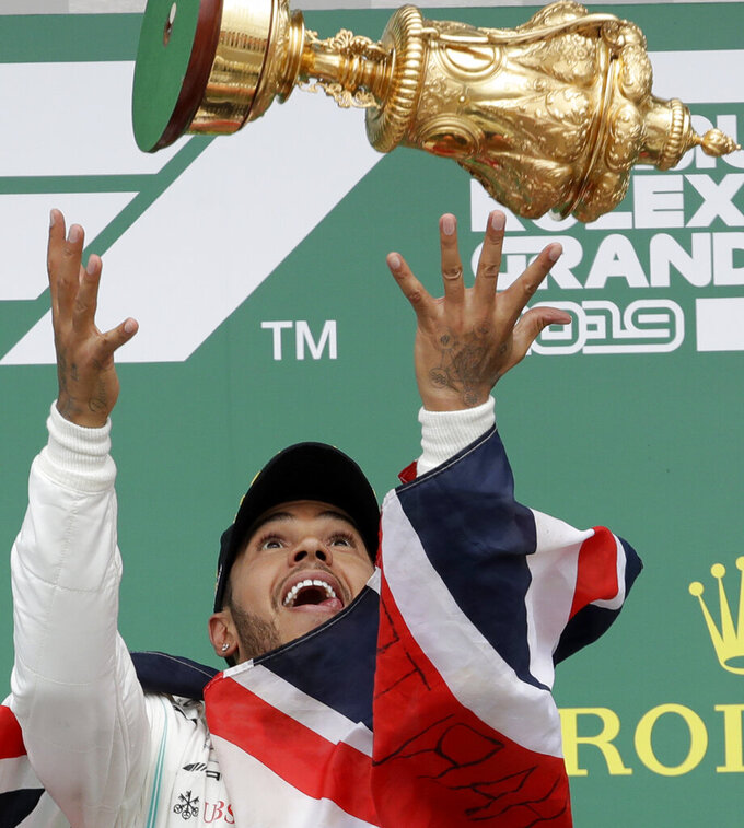 Mercedes driver Lewis Hamilton of Britain celebrates on the podium after winning the British Formula One Grand Prix at the Silverstone racetrack, Silverstone, England, Sunday, July 14, 2019. (AP Photo/Luca Bruno)