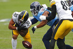 Pittsburgh Steelers running back James Conner (30) fumbles the ball as he is hit by Tennessee Titans defensive end Vic Beasley (44) in the first half of an NFL football game Sunday, Oct. 25, 2020, in Nashville, Tenn. The Steelers recovered the ball. (AP Photo/Wade Payne)