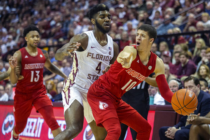 Louisville guard Samuell Williamson (10) looks for a teammate to pass to as Florida State forward Patrick Williams (4) defends in the first half of an NCAA college basketball game in Tallahassee, Fla., Monday, Feb. 24, 2020. (AP Photo/Mark Wallheiser)