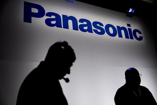 FILE - In this Jan. 4, 2017, file photo, two men are silhouetted against the Panasonic sign at CES International, in Las Vegas. Japanese electronics maker Panasonic declined to comment on reports Wednesday, Feb. 26, 2020, that it is planning to end its partnership with Tesla to produce solar panels at a factory in New York state.(AP Photo/Jae C. Hong, File)
