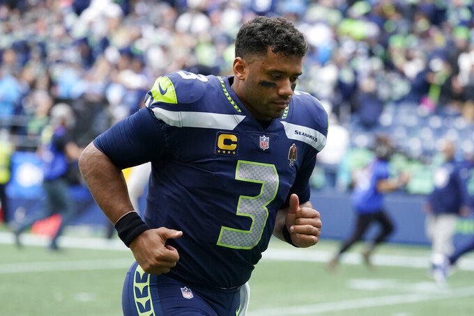 Seattle Seahawks quarterback Russell Wilson jogs off the field after an NFL football game against the Tennessee Titans, Sunday, Sept. 19, 2021, in Seattle. The Titans won 33-30 in overtime. (AP Photo/Elaine Thompson)