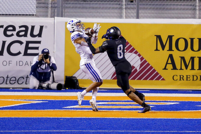 BYU wide receiver Dax Milne, left, tries to pull in a pass as Boise State cornerback Markel Reed (8) defends in the end zone during the first half of an NCAA college football game Friday, Nov. 6, 2020, in Boise, Idaho. Reed was called for pass interference. (AP Photo/Steve Conner)