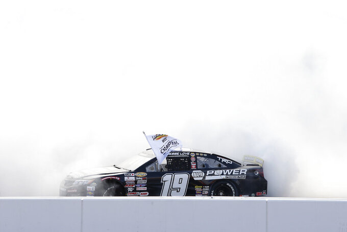 Jesse Love is engulfed in smoke as he does a burnout to celebrate his season championship during the ARCA Series auto race at Phoenix Raceway, Saturday, Nov. 7, 2020, in Avondale, Ariz. (AP Photo/Ralph Freso)