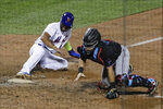 New York Mets' Amed Rosario, left, slides to home plate as Miami Marlins catcher Francisco Cervelli scrambles for the ball on a throwing error by Brian Anderson during the eighth inning of a baseball game Friday, Aug. 7, 2020, in New York. (AP Photo/Frank Franklin II)