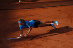 FILE - In this June 2, 2019, file photo, Greece's Stefanos Tsitsipas falls after diving to return a shot against Switzerland's Stan Wawrinka during their fourth round match of the French Open tennis tournament at Roland Garros stadium in Paris. (AP Photo/Christophe Ena, File)