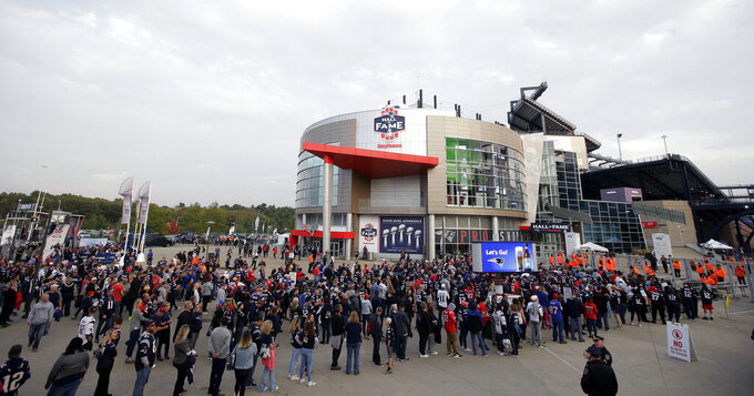 FILE - In this Oct. 4, 2018, file photo, fans line up to enter Gillette Stadium for an NFL football game between the New England Patriots and the Indianapolis Colts, in Foxborough, Mass. The crippling coronavirus pandemic has brought the entire world — including the sports world — to a standstill, and it shows no sign of going away anytime soon. The most obvious change in the short term  will be the implementation of social distancing, something that already has permeated everyday life. Ticket sales will be capped and fans will be given an entrance time to prevent crowds at the gate.  (AP Photo/Steven Senne, File)