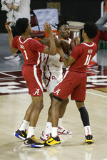 Oklahoma's Victor Iwuakor (0) fights for the ball with Alabama's Herbert Jones (1) and Joshua Primo (11) during the first half of an NCAA college basketball game in Norman, Okla., Saturday, Jan. 30, 2021. (AP Photo/Garett Fisbeck)