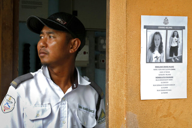 FILE - In this Aug. 11, 2019, file photo, a security guard stands next to a notice showing Nora Anne Quoirin, in Seremban, Malaysia. A Malaysian coroner ruled Monday, Jan. 4, 2021 the death of the French-Irish teen, whose body was found near a Malaysian jungle resort where she vanished while on holiday, was most likely a misadventure that didn't involve other people. (AP Photo/FL Wong, File)