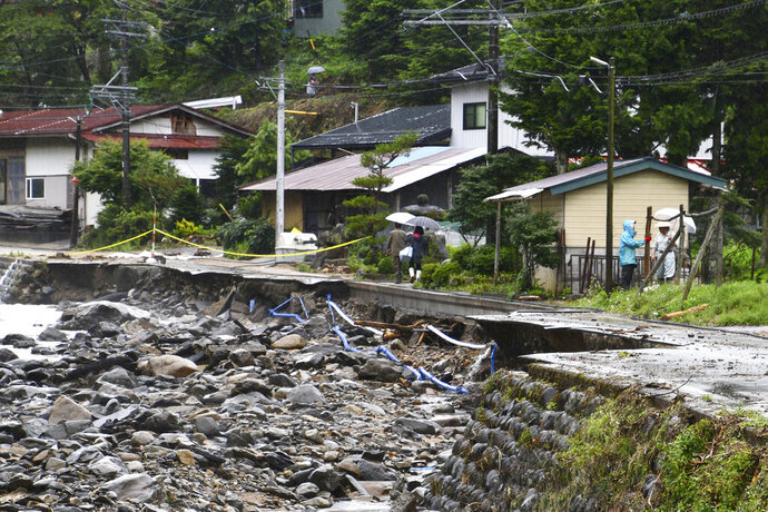 People walk on a road damaged by water following a heavy rain in Takayama, Gifu prefecture, central Japan Friday, July 10, 2020. Parts of Nagano and Gifu, including areas known for scenic mountain trails and hot springs, have been flooded by massive downpours that have lasted for nearly a week. (Kyodo News via AP)