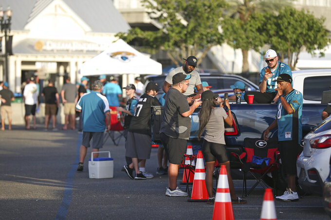 Fans tailgate outside of TIAA Bank Field before an NFL football game between the Jacksonville Jaguars and the Miami Dolphins, Thursday, Sept. 24, 2020, in Jacksonville, Fla. (AP Photo/Stephen B. Morton)