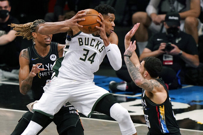 Milwaukee Bucks forward Giannis Antetokounmpo (34) drives around Brooklyn Nets forward Nicolas Claxton (33) as Nets guard Mike James (55) defends during the third quarter of Game 2 of an NBA basketball second-round playoff series, Monday, June 7, 2021, in New York. (AP Photo/Kathy Willens)