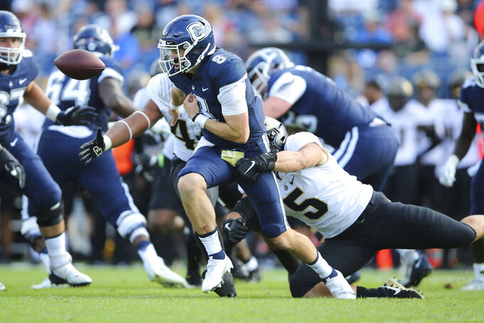 Purdue defensive end George Karlaftis (5) knocks the ball free from Connecticut quarterback Steven Krajewski (8) during the first half of an NCAA football game on Saturday, Sept. 11, 2021, in East Hartford, Conn. (AP Photo/Stew Milne)