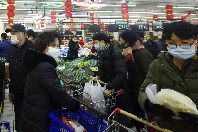 People wearing masks buy foods at a supermarket in Hangzhou in east China's Zhejiang province, Saturday, Feb. 8, 2020. China's communist leaders are striving to keep food flowing to crowded cities despite anti-disease controls, to quell fears of possible shortages and stave off price spikes from panic buying after most access to Wuhan was cut off Jan. 23. Food stocks in supermarkets ran low shortly after Beijing imposed travel curbs and extended the Lunar New Year holiday to keep factories, offices and other businesses closed and the public at home, attempting to prevent the virus from spreading. (Chinatopix via AP)
