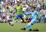 Vancouver Whitecaps goalie Zac MacMath, right, kicks the ball just past Seattle Sounders' Justin Dhillon in the first half of an MLS soccer match Saturday, June 29, 2019, in Seattle. (AP Photo/Elaine Thompson)