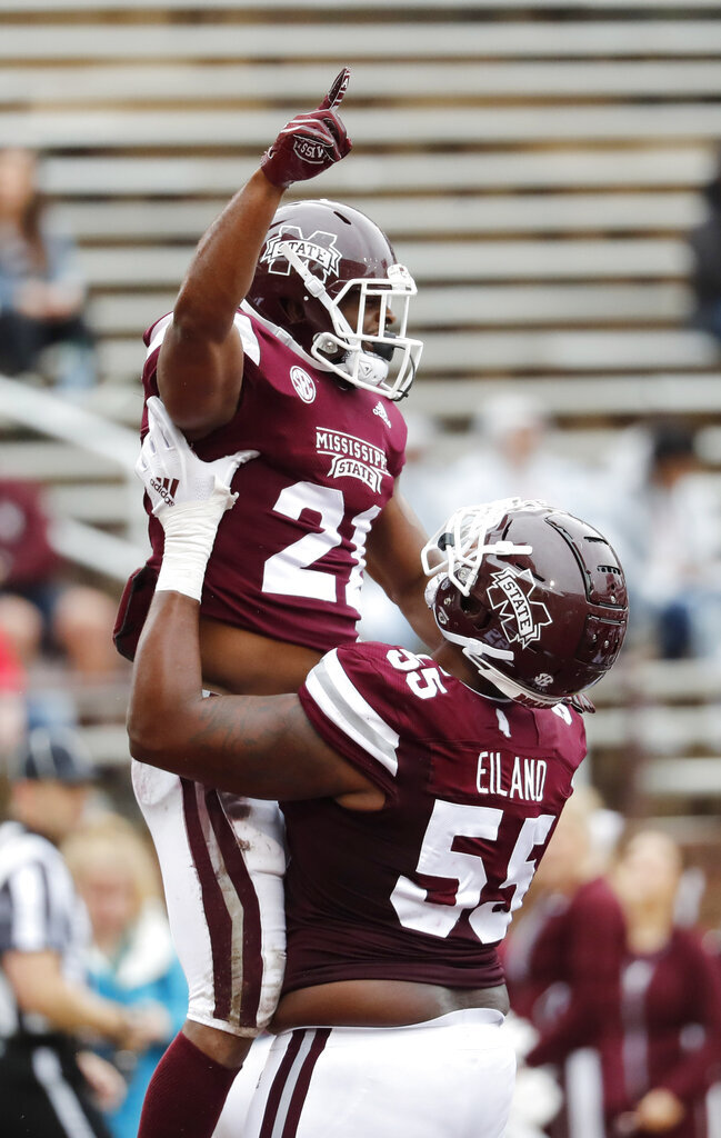 Mississippi State running back Nick Gibson (21) and offensive lineman Greg Eiland (55) celebrate Gibson's 5-yard touchdown run during the team's spring NCAA college football game in Starkville, Miss., Saturday, April 13, 2019. (AP Photo/Rogelio V. Solis)