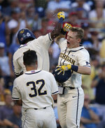 Michigan's Jimmy Kerr, right, celebrates after hitting a 2-run home run against Vanderbilt during the seventh inning in Game 1 of the NCAA College World Series baseball finals in Omaha, Neb., Monday, June 24, 2019. (AP Photo/Nati Harnik)