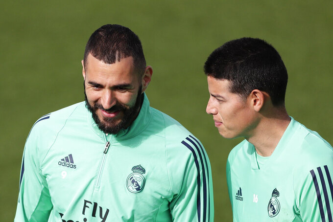 Real Madrid's Karim Benzema, left, and Real Madrid's James Rodriguez take part in a training session at the team's Valdebebas training ground in Madrid, Spain, Tuesday, Feb. 25, 2020. Real Madrid will play against Manchester City in a Champions League soccer match on Wednesday. (AP Photo/Manu Fernandez)