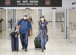 Mike Rustici, left, and Linda Scruggs exit customs after arriving on a flight from Lima, Peru, Saturday, March 21, 2020, at Miami International Airport in Miami. The pair's plight illustrates the desperation people stuck abroad experienced as the COVID-19 pandemic spread. Peru confirmed its first case of the virus on March 6. By the time Scruggs and Rustici arrived a week later, it was spreading. (AP Photo/Wilfredo Lee)