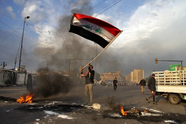 A protester waves the national flag while demonstrators set fire to close streets near Tahrir Square during a demonstration against the Iranian missile strike in Baghdad, Iraq, Wednesday, Jan. 8, 2020. Iran struck back at the United States early Wednesday for killing a top Revolutionary Guard commander, firing a series of ballistic missiles at two military bases in Iraq that house American troops in a major escalation between the two longtime foes. (AP Photo/Khalid Mohammed)