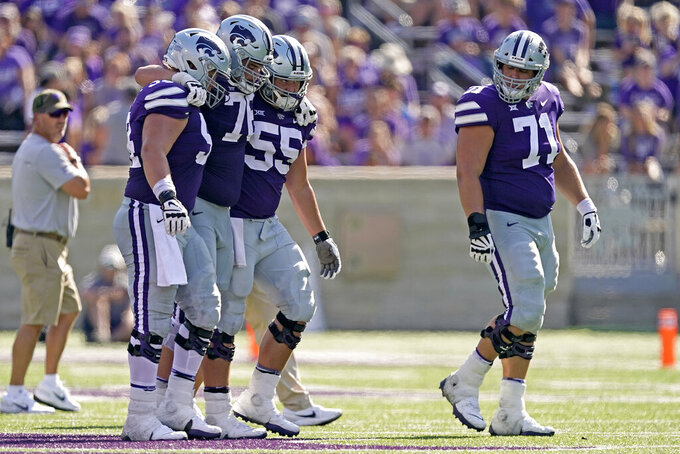 Kansas State offensive lineman Josh Rivas, second from left, is helped off the field after getting injured during the second half of an NCAA college football game against Nevada Saturday, Sept. 18, 2021, in Manhattan, Kan. (AP Photo/Charlie Riedel)