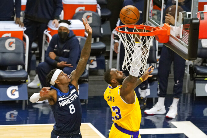 Los Angeles Lakers' LeBron James (23) lays up to score as Minnesota Timberwolves' Jarred Vanderbilt (8) looks on in the second half of an NBA basketball game, Tuesday, Feb. 16, 2021, in Minneapolis. The Lakers won 112-104.James scored 30 points. (AP Photo/Jim Mone)