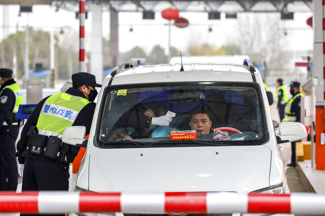A policeman uses a digital thermometer to take a driver's temperature at a checkpoint at a highway toll gate in Wuhan in central China's Hubei Province, Thursday, Jan. 23, 2020. China closed off a city of more than 11 million people Thursday in an unprecedented effort to try to contain a deadly new viral illness that has sickened hundreds and spread to other cities and countries amid the Lunar New Year travel rush. (Chinatopix via AP)