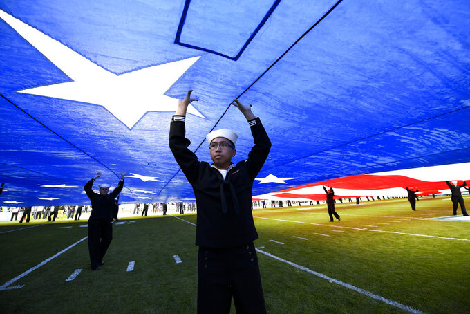 United States Navy sailors hold up a giant U.S. flag before the Holiday Bowl NCAA college football game between Utah and Northwestern, Monday, Dec. 31, 2018, in San Diego. (AP Photo/Denis Poroy)