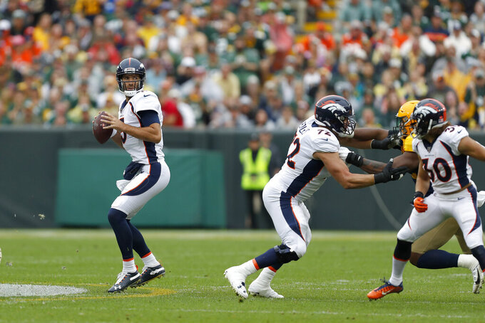 Denver Broncos quarterback Joe Flacco, left, drops back to pass during the first half of an NFL football game against the Green Bay Packers, Sunday, Sept. 22, 2019, in Green Bay, Wis. (AP Photo/Matt Ludtke)