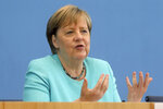 German Chancellor Angela Merkel, gestures, as she holds her annual summer news conference in Berlin, Germany, Thursday, July 22, 2021.  Merkel said Thursday that new coronavirus infections in Germany are once again rising at worrying speed. She appealed to her compatriots to get vaccinated and persuade others to do so. (Wolfgang Kumm/dpa via AP)
