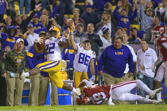 LSU running back Clyde Edwards-Helaire (22) gets away from Arkansas defensive back Myles Mason (18) on a touchdown run during the second half of an NCAA college football game in Baton Rouge, La., Saturday, Nov. 23, 2019. (AP Photo/Matthew Hinton)