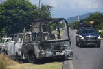 A charred truck that belongs to Michoacan state police sits on the side of the road after it was burned during an attack, as state police drive past in El Aguaje, Mexico, Monday, Oct. 14, 2019. At least 13 police officers were killed and three others injured Monday in the ambush. (AP Photo/Armando Solis)