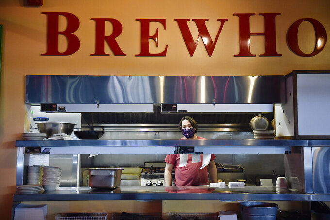 A cook at Brewhouse Pub and Grille in Helena checks on a food order Monday, May 4, 2020, the first day restaurants are authorized to serve sit-down customers since Gov. Steve Bullock ordered them closed on March 20.   (Thom Bridge/Independent Record via AP)
