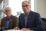 Roger Millar, Washington state secretary of transportation, left, listens as Washington Gov. Jay Inslee speaks to the media before Governor Inslee and Oregon Gov. Kate Brown signed a memorandum of intent to replace the Interstate 5 bridge during an event in Vancouver, Wash., Monday, Nov. 18, 2019. (Nathan Howard/The Columbian via AP)