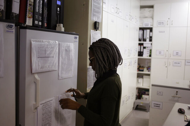 FILE - In a Nov. 30, 2016 file photo, pharmacist Mary Chindanyika looks at documents on a fridge containing a trial vaccine against HIV on the outskirts of Cape Town, South Africa. The latest attempt at an HIV vaccine has failed. Researchers announced Monday, Feb. 3, 2020 they've stopped giving the experimental shots in a major study in South Africa, which has one of the world's highest HIV rates. (AP Photo/Schalk van Zuydam, File)