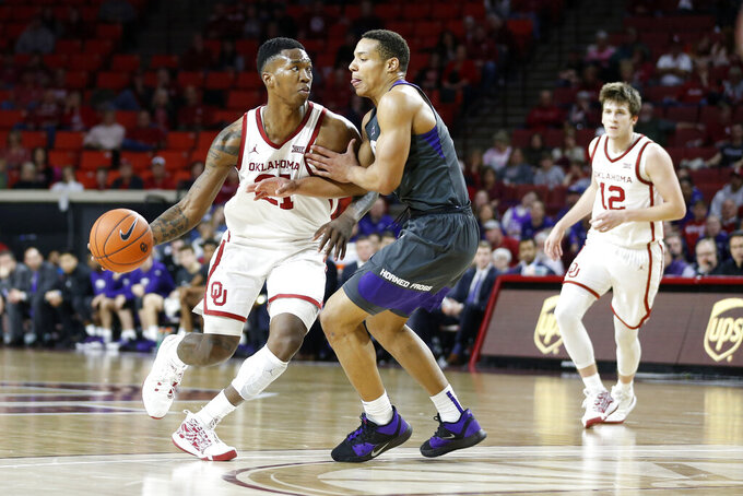Oklahoma's Kristian Doolittle (21) drives against TCU's Desmond Bane (1) as Oklahoma's Austin Reaves (12) looks on during the second half of an NCAA college basketball game in Norman, Okla., Saturday, Jan. 18, 2020. (AP Photo/Garett Fisbeck)