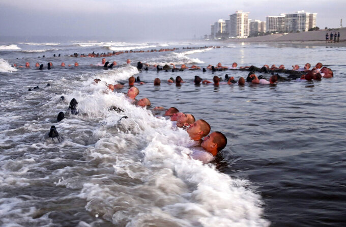 """FILE - In this May 4, 2020, photo provided by the U.S. Navy, SEAL candidates participating in """"surf immersion"""" during Basic Underwater Demolition/SEAL (BUD/S) training at the Naval Special Warfare (NSW) Center in Coronado, Calif. The Navy never had to look too hard to fill its elite SEAL force. For years, eager recruits poured in to try out for special warfare teams, but they were overwhelmingly white. Now, Naval Special Warfare Command leaders are trying to turn that around, developing programs to seek out recruits from more diverse regions of the country. (MC1 Anthony Walker/U.S. Navy via AP)"""