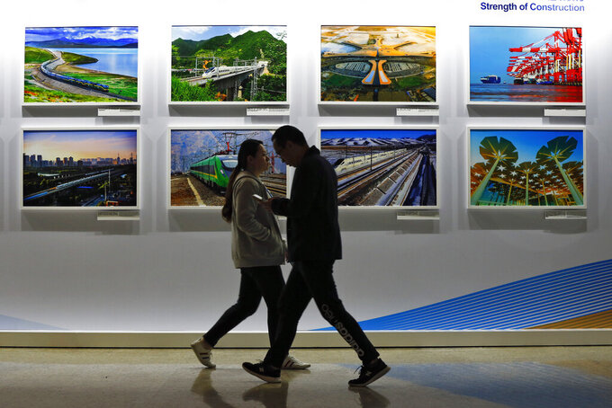 FILE - In this Saturday, April 27, 2019 file photo, people walk by a display board showcasing China's sweeping infrastructure-building projects at the media center of the Belt and Road Forum in Beijing. African leaders in 2020 are asking what China can do for them as the coronavirus pandemic threatens to destroy economies across a continent where Beijing is both the top trading partner and top lender. (AP Photo/Andy Wong, File)