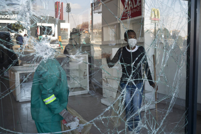 Volunteers participate in the cleaning efforts at Soweto's Diepkloof mall outside Johannesburg, South Africa, Thursday July 15, 2021. A massive cleaning effort has started following days of violence in Gauteng and KwaZulu-Natal provinces. The violence erupted last week after Zuma began serving a 15-month sentence for contempt of court for refusing to comply with a court order to testify at a state-backed inquiry investigating allegations of corruption while he was president from 2009 to 2018. (AP Photo/Jerome Delay)