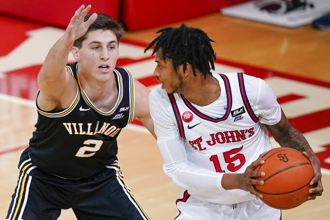 Villanova's Collin Gillespie (2) defends against St. John'sVince Cole (15) during the first half of an NCAA college basketball game Wednesday, Feb. 3, 2021, in New York. (AP Photo/Frank Franklin II)
