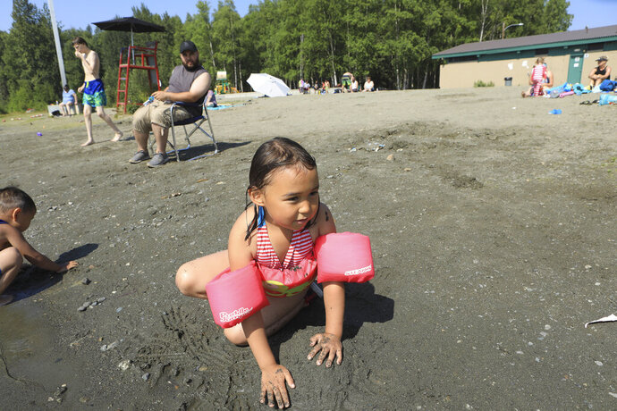 Milana Acuna, 5, makes a mud creation at the beach at Goose Lake as her father, Manny Acuna, looks on on Friday, July 5, 2019, at Jewel Lake in Anchorage, Alaska. The official temperature on Thursday, July 4, reached 90 degrees for the first time in Anchorage and hot weather is expected to continue into next week. (AP Photo/Dan Joling)