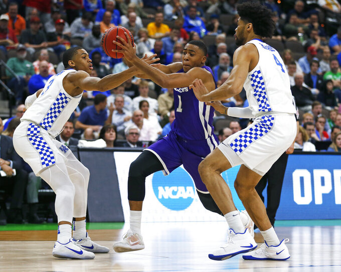 Abilene Christian's Jaren Lewis (1) moves between Kentucky's Keldon Johnson, left, and Nick Richards (4) during the first half of a first-round game in the NCAA men's college basketball tournament in Jacksonville, Fla., Thursday, March 21, 2019. (AP Photo/Stephen B. Morton)