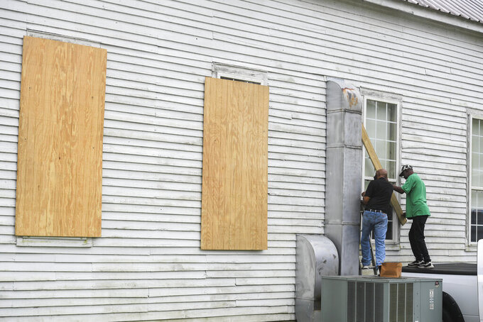 The Rev. Ivory Williams, Sr. and Chris Welch board up the windows of St. John Baptist Church while prepping for Hurricane Delta on Thursday, Oct. 8, 2020, in Charenton, La. (Brad Kemp/The Advocate via AP)