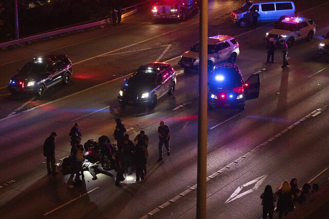 Emergency workers tend to an injured person on the ground after a driver sped through a protest-related closure on the Interstate 5 freeway in Seattle, authorities said early Saturday, July 4, 2020. Dawit Kelete, 27, has been arrested and booked on two counts of vehicular assault. (James Anderson via AP)