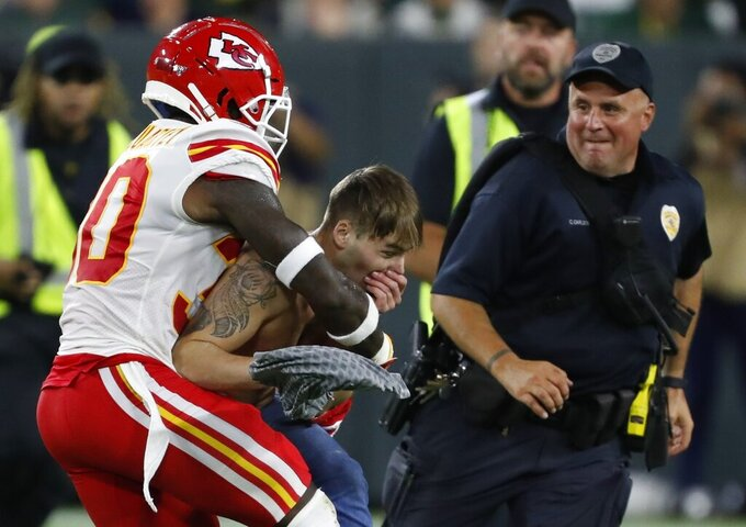 Kansas City Chiefs' Harold Jones-Quartey takes a fan that ran on the field during the second half of a preseason NFL football game against the Green Bay Packers Thursday, Aug. 29, 2019, in Green Bay, Wis. (AP Photo/Matt Ludtke)