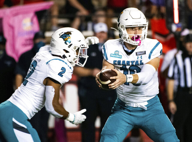 Coastal Carolina quarterback Grayson McCall (10) hands off the football to running back Reese White (2) during the first half of an NCAA football game against Louisiana-Lafayette in Lafayette, La., Wednesday, Oct. 14, 2020. (AP Photo/Paul Kieu)